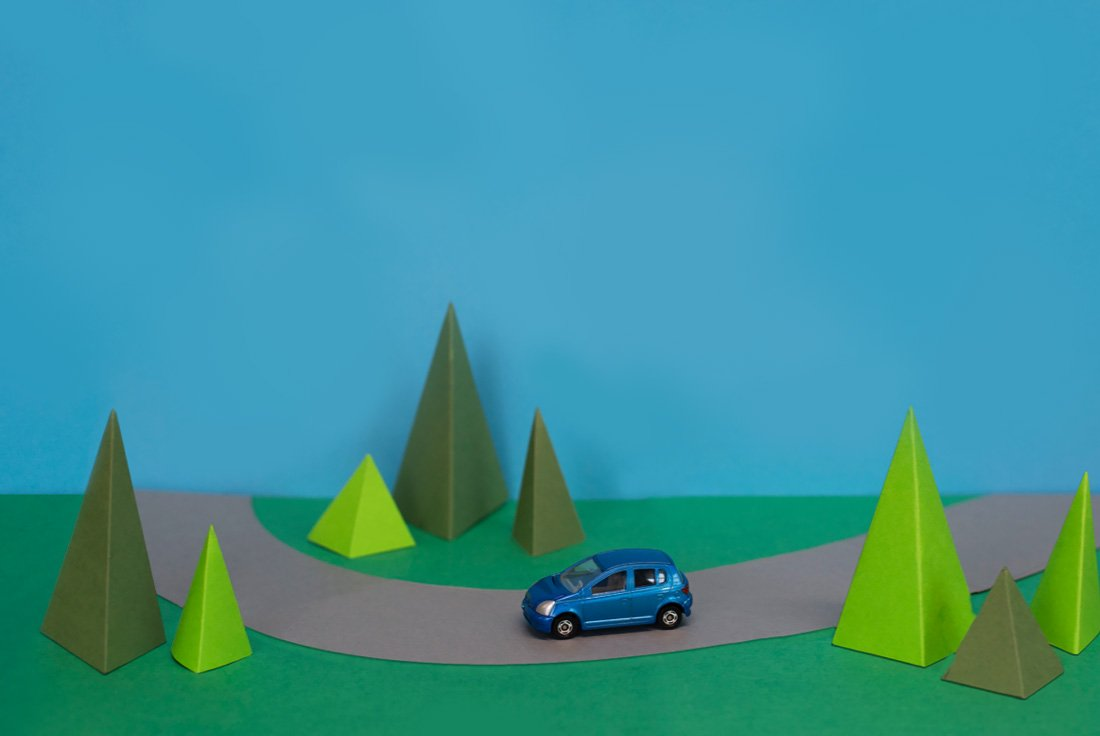 Toy blue car driving through paper-made scenery, surrounded by triangular paper trees.