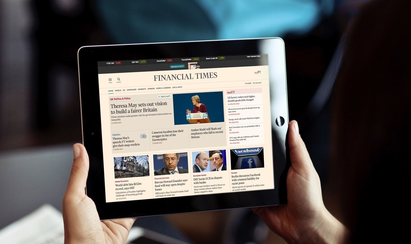 A pair of hands holding an Ipad with the Financial Times page open