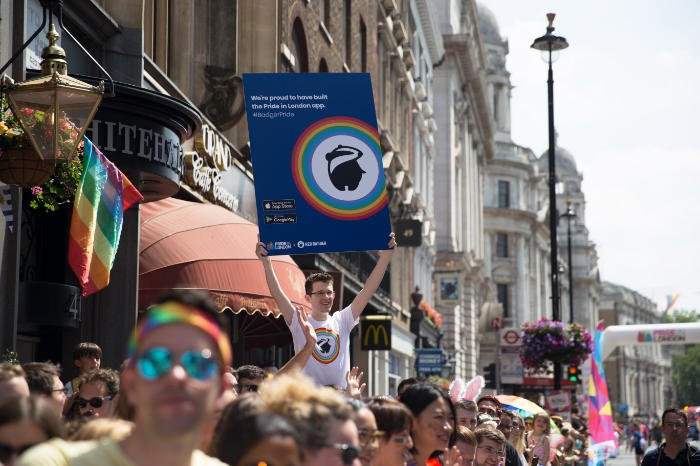 People celebrating at the Pride parade./ A young man holding up a big promotional poster at the Pride Parade.