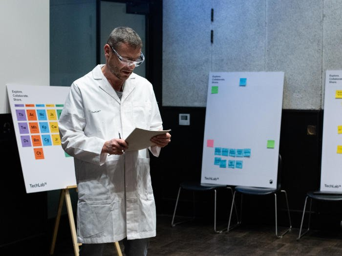 Stuart Harris, Red Badger co-founder and chief scientist in a lab coat reading a report.